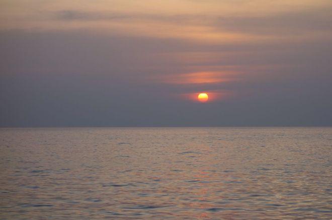 Den första av hittills tre solnedgångar. Skymning över havet, svalkan när solens strålar viker av. Kväll på stranden är härligt.