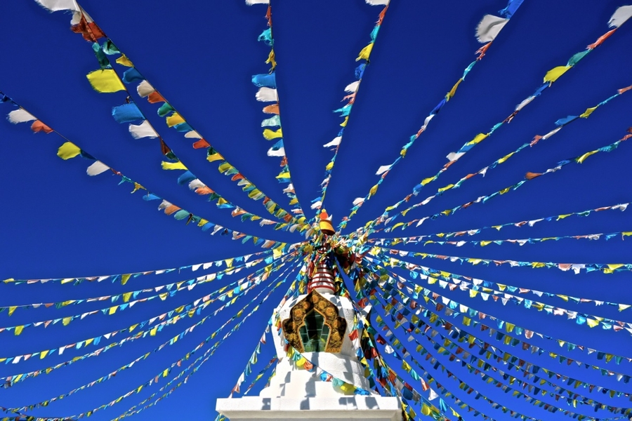 Tibetansk buddistiska böneflaggor hänger från toppen av en stupa utanför fantasistaden Shangri-La. På högplatån läser vinden de trycka bönerna och sänder ut deras budskap om visdom och medkänsla över världen. Ta tillvara på världen, för den är en oändlig källa kunskap.