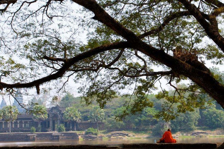 En munk vilar fötterna utanför Angkor Wats vallgrav.