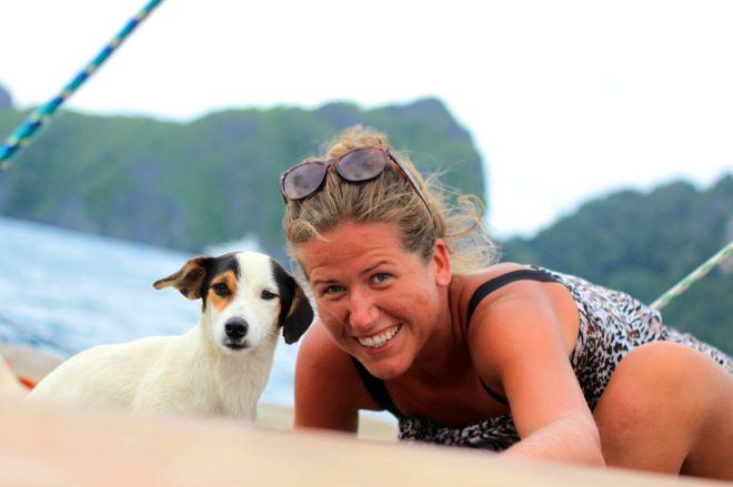 En människa med vindpinat hår och sneda ögonbryn som har det bra tillsammans med en hund som har det bra trots att hans öron blåser omkring.