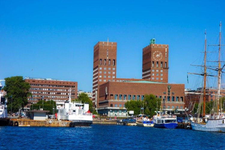 Rådhusplassen sett från vattnet. Det är en uppställning av gamla skepp och nya snabbfärjor.